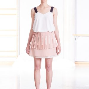 White cami top with black straps and short pleated pale pink skirt